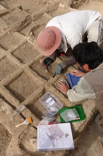 Des membres de la mission archéologique inspectent les vestiges d'un jardin funéraire millénaire à Louxor.