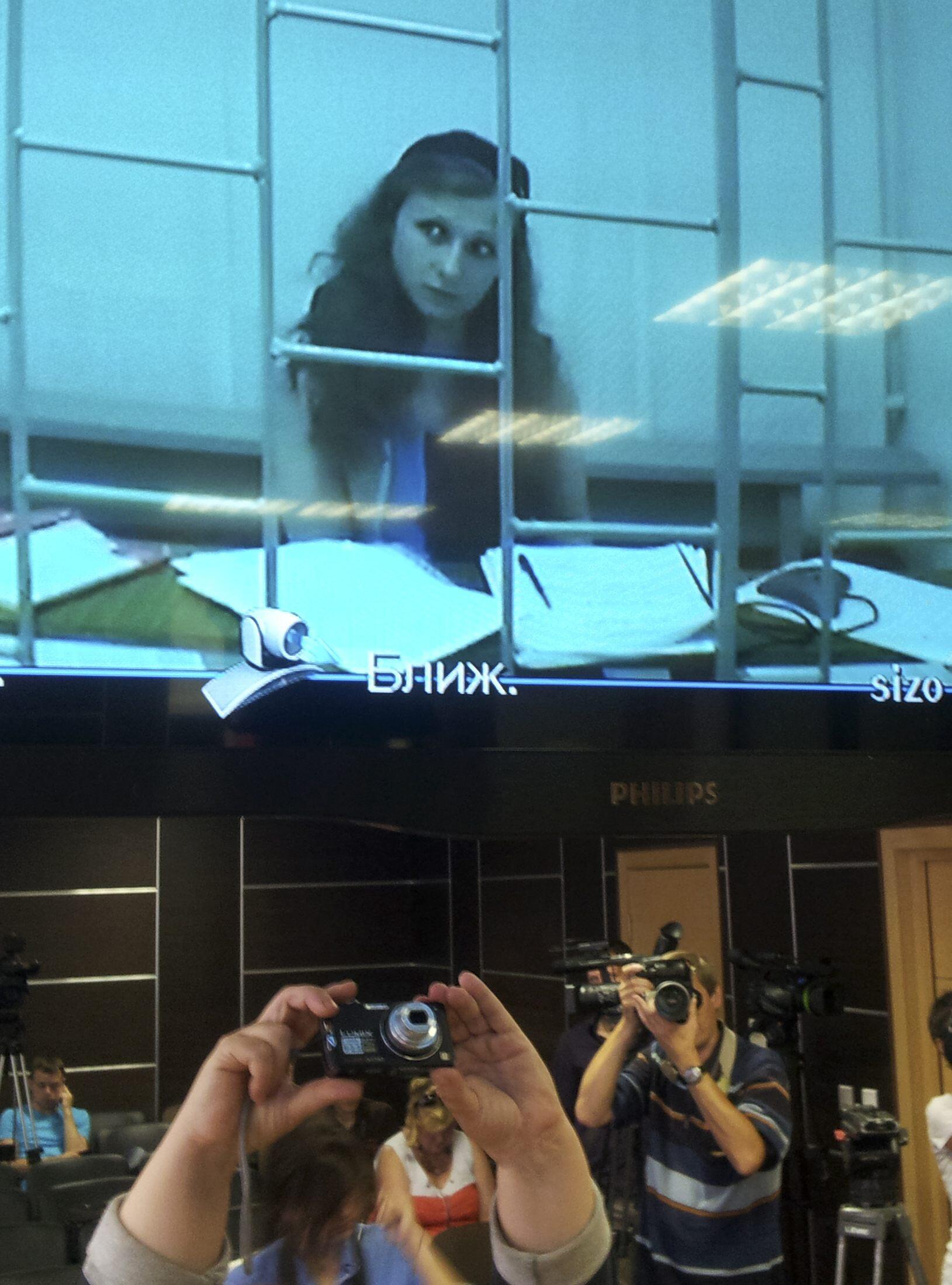 Maria Alekhina aparece em uma tela durante julgamento em tribunal russo nesta quarta-feira, 24 de julho.