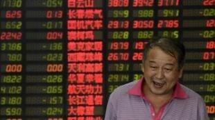 Un inversionista frente a la pizarra de cotizaciones de la bolsa en una casa de corretaje, Shanghai, 18 de agosto de 2015.