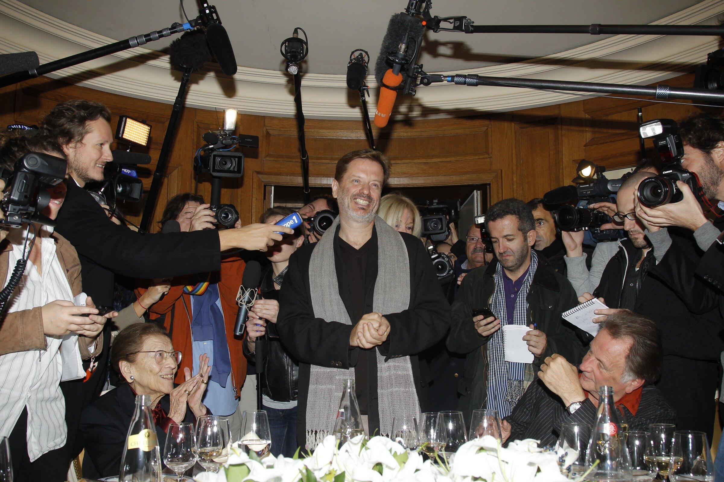 O escritor francês Alexis Jenni, ao centro, durante coletiva de imprensa em Paris, após anúncio do prêmio Goncourt.
