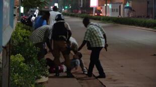 Des policiers prennent en charge une personne blessée, lors de l'attaque du dimanche 13 août 2017 à Ouagadougou.