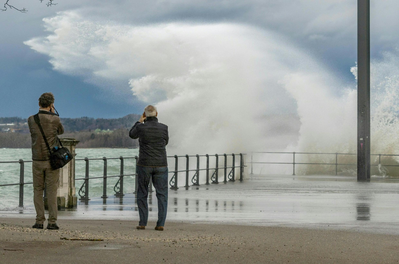 Dois homens registram imagens das ondas formadas pela tempestade Ciara no Lago de Constânça, na localidade de Bregenz, na Áustria.