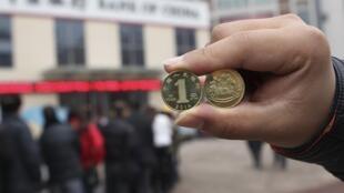 Chinês mostra moeda comemorativa do ano do cavalo, enquanto pessoas fazem fila diante de banco; a aceleração do consumo interno é um dos objetivos das autoridades chinesas para garantir o crescimento do país.