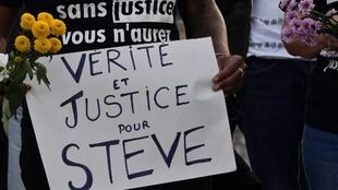 "A woman holds a placard reading ""Truth and justice for Steve"" as activists from French associations ""Clap33"" and ""Collectif Quatre Couleurs"" gather to pay a tribute on July 30, 2019, in Bordeaux, southwestern France."