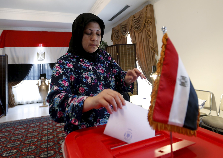 Eleitora vota neste domingo em uma urna na embaixada do país no Bahrein.