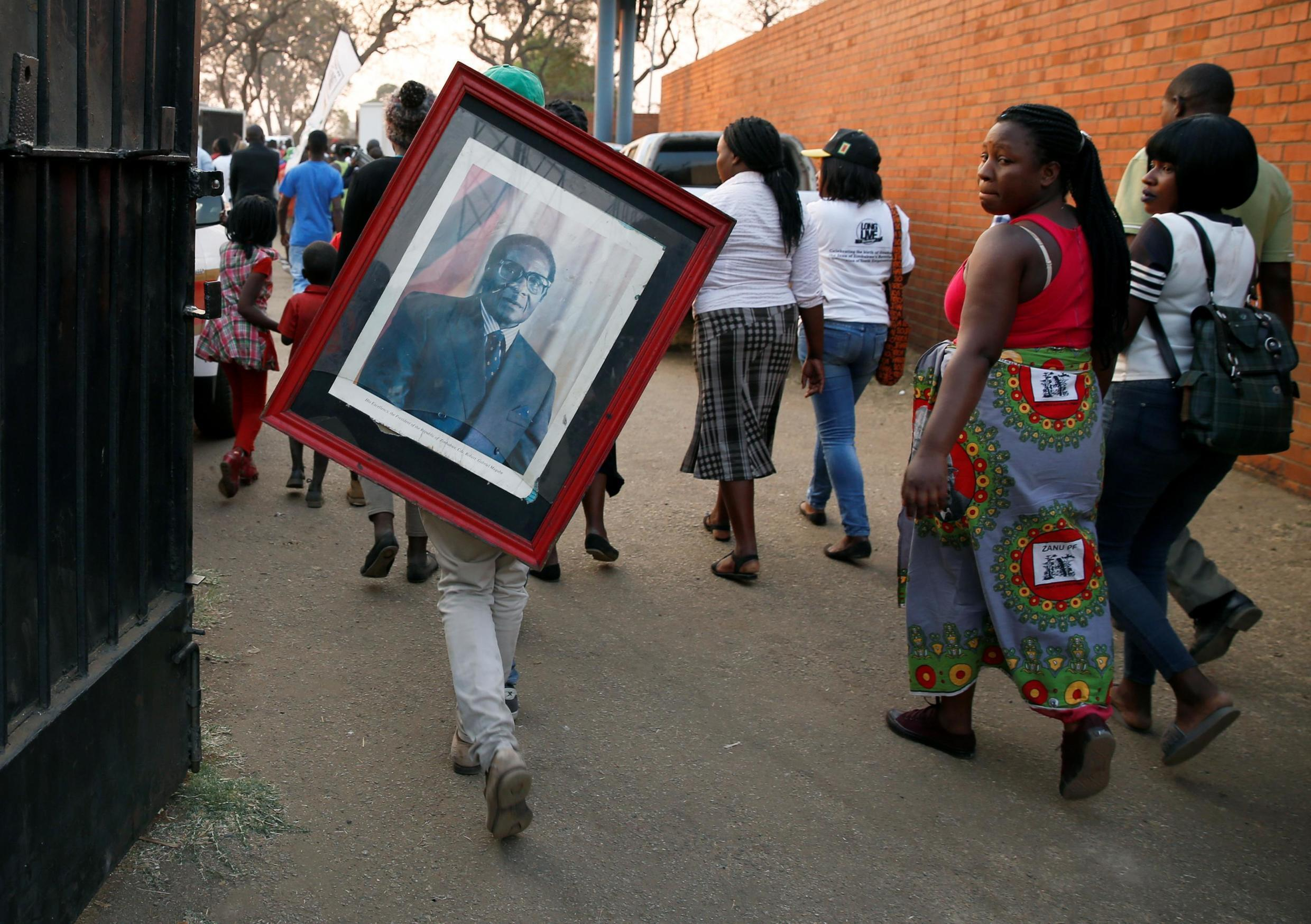 Supporters of the late Zimbabwean president Robert Mugabe leave the stadium in Harare, 12 September 2019.