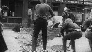 Los estudiantes arrancan las rejas de protección de los árboles en París en el 68. Captura de la película 'Joli mois de Mai' ARC.