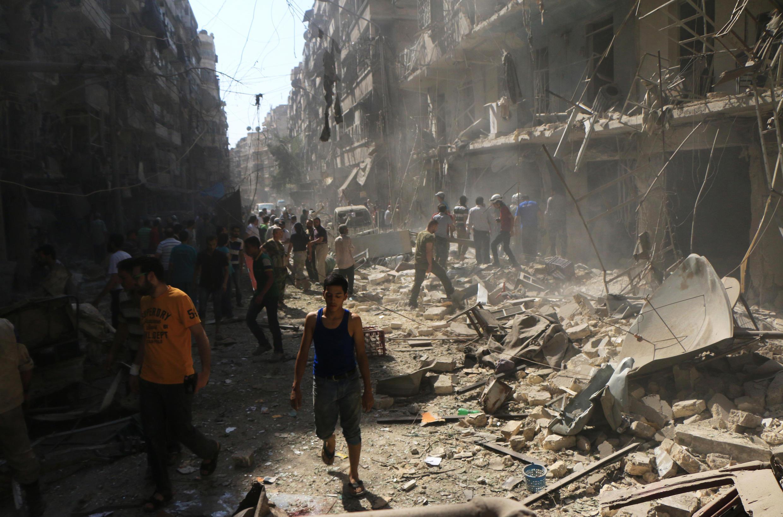 Sírios em meio aos escombros no bairro de Shaar, na cidade de Aleppo, depois de um ataque aéreo das forças do governo. 17 setembro de 2015.