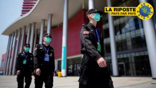 En Chine, des agents de sécurité patrouillent devant le centre de convention de Wuhan, transformé en hôpital pendant la crise sanitaire, le 9 avril 2020.