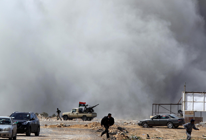 Rebeldes corren para protegerse durante un bombardeo de fuerzas leales a Kadafi en el checkpoint de Al Ugaila, entre las ciudades de Brega y Ras Lanuf.