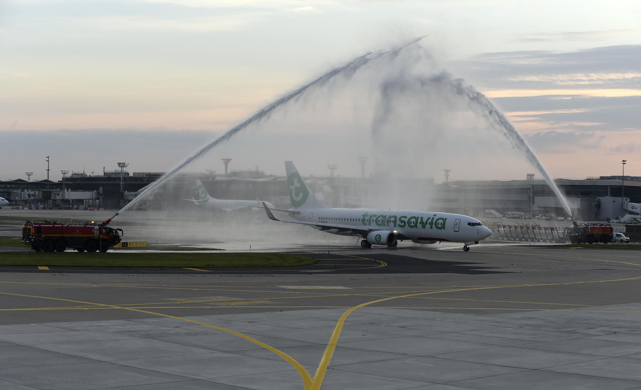 Firefighters salute a Transavia Boeing 737-800 with water spraying as it becomes the first flight in three months to take off from Paris' Orly airport on June 26, 2020.