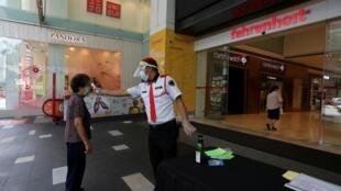 Un vigile prend la température d'une cliente à l'entrée d'un centre commercial à Kuala Lumpur, en Malaisie.