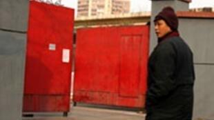 """2009年二月八日上访维权代表郑大靖站在曾经遭酷刑""""黑监狱""""门前。"""