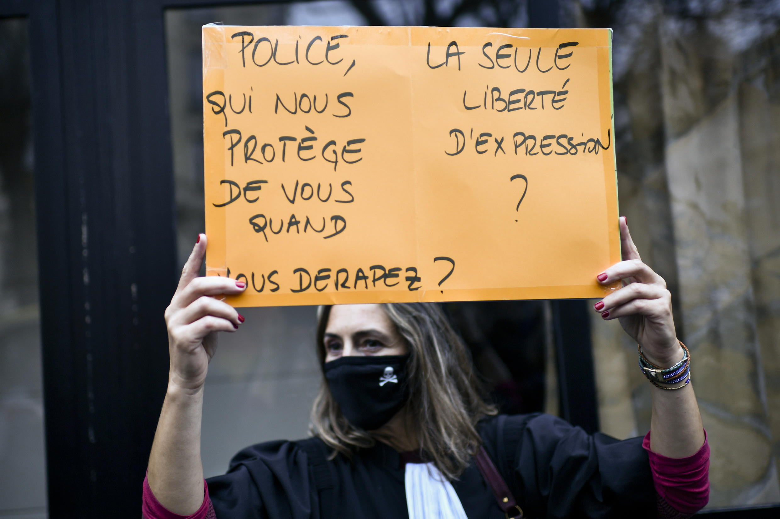 """French police have long been accused of using heavy-handed tactics. A protestor in lawyer's garb holds a sign reading """"Police, who will protect us when you misbehave ?"""" during a rally against the comprehensive security bill debated in parliament."""