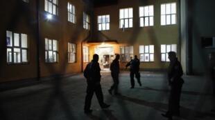 Полицейское оцепление здания школы, где расположен избирательный участок, на который было совершено нападение. Митровица 03/11/2013