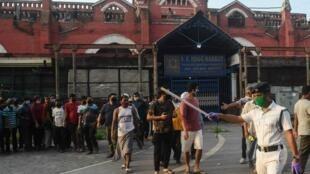Jami'an 'Yan Sandan India, yayin kokarin hana mutane karya dokar takaita cinkoson jama'a, yayin da suke kan layin sayen barasa, a Kolkata. 4/5/2020.