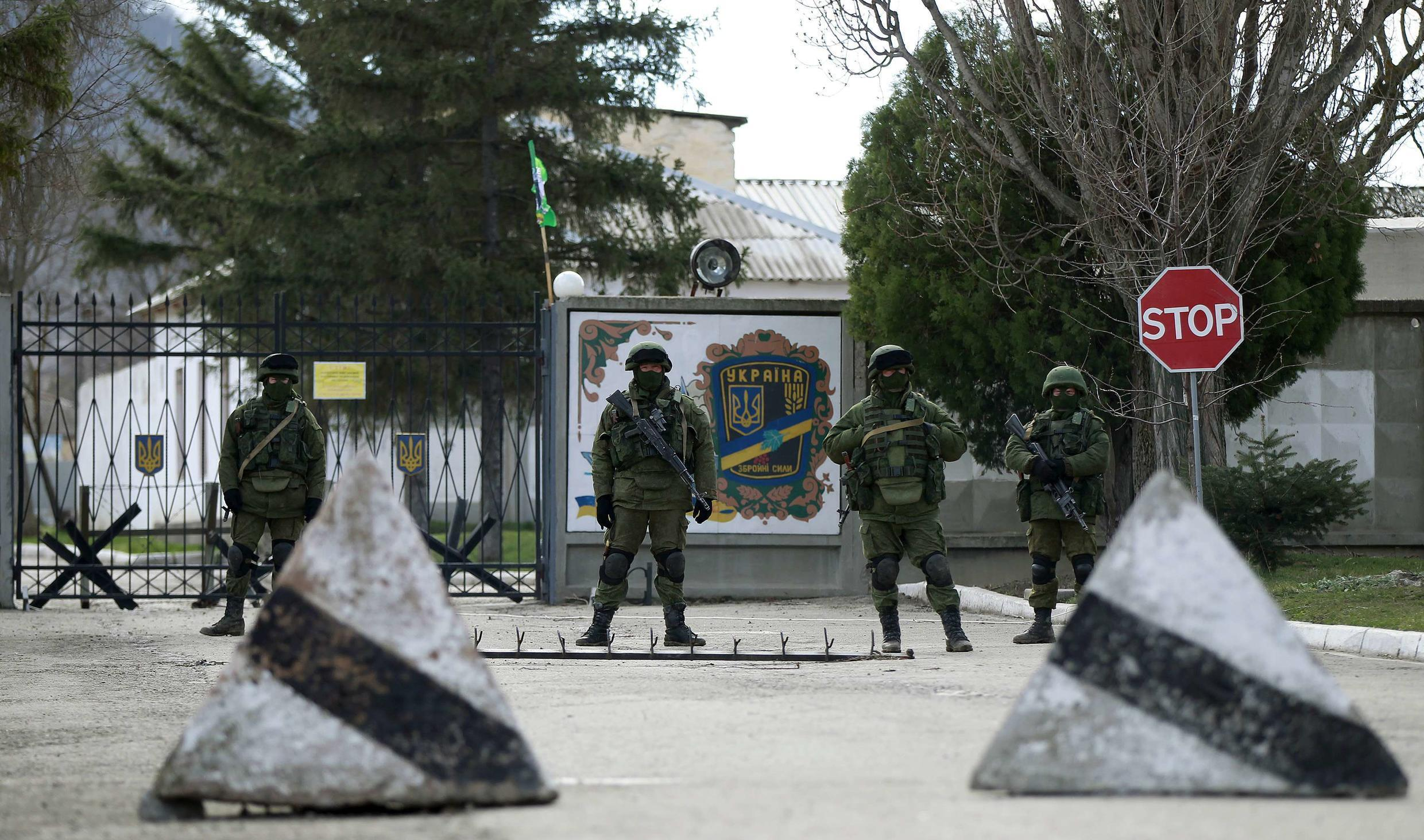 Armed men, believed to be Russians, stand guard near the Ukrainian military base outside Simferopol, 17 March 2014.