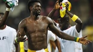 Togo's Emmanuel Adebayor celebrates getting through to the next round after drawing their Group D football match against Tunisia
