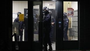 French police officers enter an apartment building during clashes in Villeneuve-la-Garenne, in the northern suburbs of Paris, early on April 21, 2020.  Tension with the police erupted again on the evening of April 20 in Villeneuve-la-Garenne near Paris, where a motorcycle accident involving the police had provoked the first clashes with residents two days before.