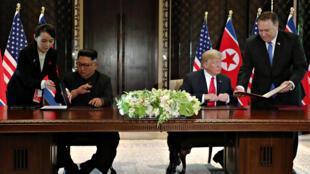 Lãnh đạo Bắc Triều Tiên Kim Jong Un (T) và tổng thống Mỹ Donald Trump ký thông cáo chung sau cuộc gặp thượng đỉnh, Singapore, ngày 12/06/2018