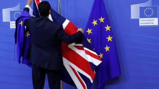 Un empleado prepara la presentación de las banderas en vista de la primera vuelta de las negociaciones sobre el brexit en Bruselas, el 17 de julio de 2017.