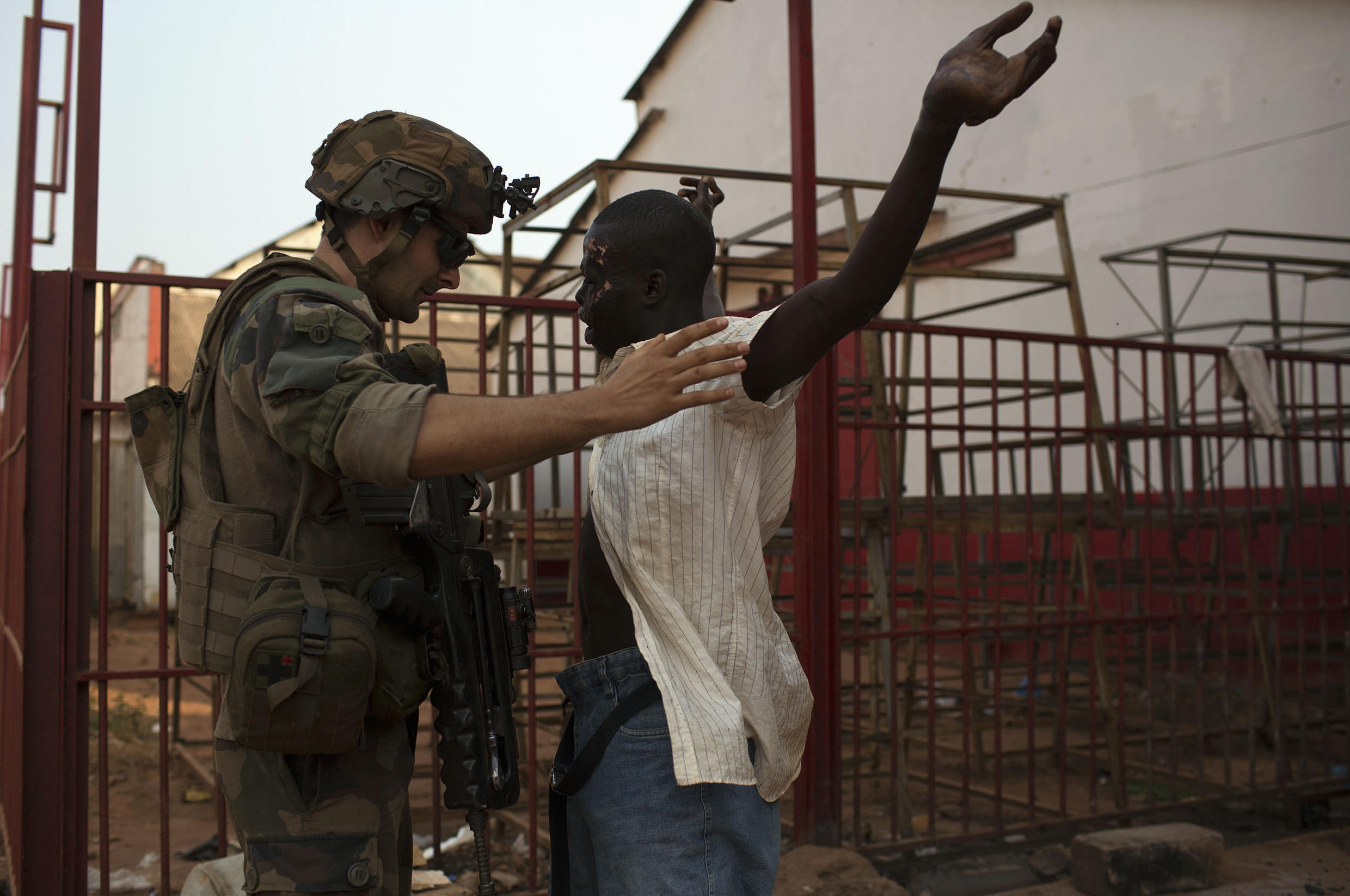 A French soldier frisks a man in Bangui