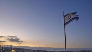 Una bandera de Israel ondea en el monte de los Olivos con una vista general de Jerusalén al fondo, el 23 de septiembre de 2020