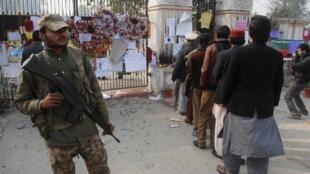 Un soldat monte la garde devant la porte de l'école attaquée par des talibans, en décembre 2014.