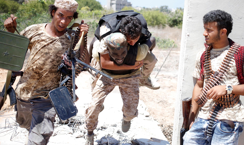 Un soldat des forces loyales au gouvernement libyen d'union nationale ramène sur son dos un camarade blessé lors d'un combat face au groupe EI, à Syrte.