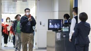 Des passagers d'un vol provenant de Wuhan sont contrôlés par des scanners thermiques à leur arrivée à l'aéroport de Taipei, le 13 janvier 2020.