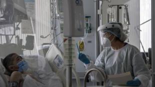 Una médica sostiene un celular mientras un joven de 21 años en cuidados intensivos por covid-19 se comunica por videollamada con su familia desde el hospital público El Tunal, en Bogotá