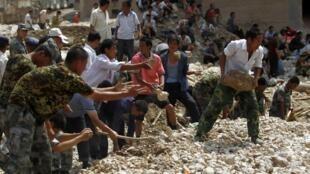 Dans le district de Zouqhu, le 9 août 2010, les secouristes travaillent à la pelle ou à mains nues, sans équipement  lourd dont l'épaisseur de la boue empêcherait toute manoeuvre.