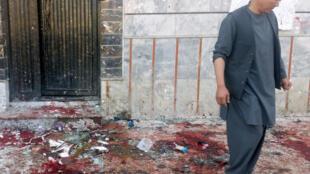 Um homem caminha pelo local onde houve o ataque suicida num centro eleitoral de Cabul, Afeganistão , em 22 de abril de 2018