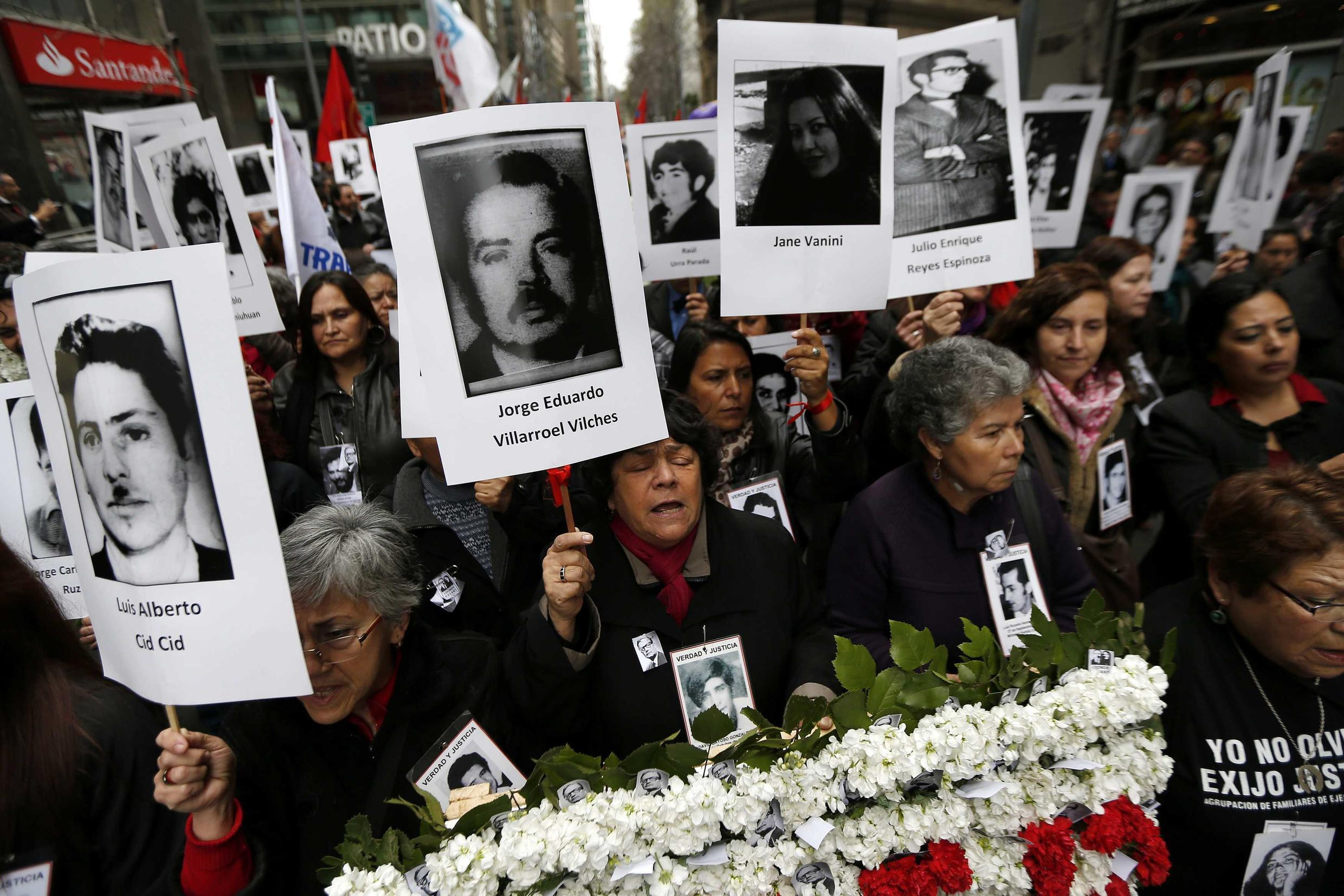 Demonstrators hold up images of their relatives, victims of human rights abuse during the Pinochet years, Santiago, 11 September, 2013
