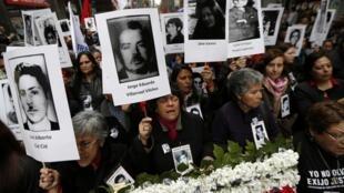 Des manifestants brandissent des portraits de proches, victimes de violations des droits de l'homme durant la dictature Pinochet lors d'un rassemblement à Santiago du Chili, le 11 septembre 2013.