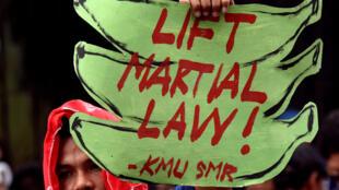 Un opposant à la loi martiale manifeste lors d'une session de la Chambre des représentants à Manille, le 22 juillet 2017. «Levez la loi martiale», peut-on lire sur sa pancarte.