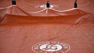 Personal del torneo retira una lona protectora de la pista Suzanne Lenglen después de que lloviera durante una jornada de la última edición del Roland Garros, el 4 de octubre de 2020 en París