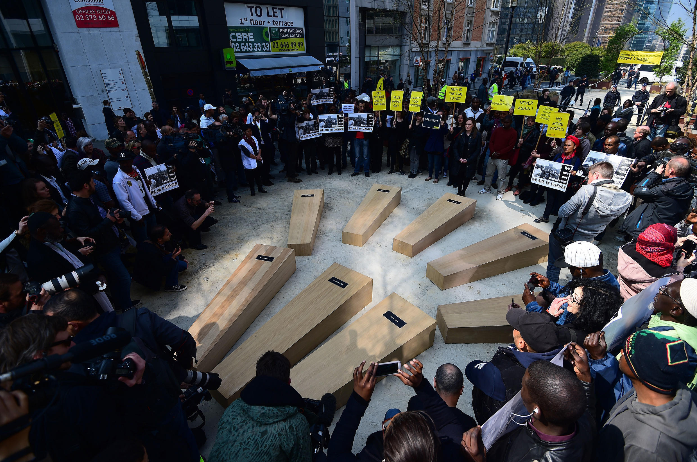 Des migrants et des activistes autour de faux cercueils, pour dénoncer la crise.