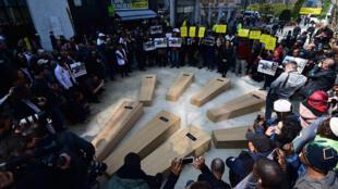 Des migrants et des activistes d'Amnesty se rassemblent autour de faux cercueils, après une « marche funèbre », pour dénoncer la crise humanitaire en Méditerranée, le 23 avril 2015.