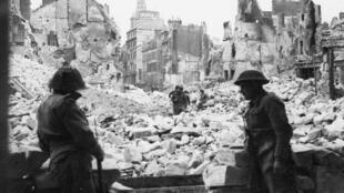 Troupes britanniques devant la cathédrale de Caen après avoir délogé les troupes allemandes, juillet 1944.