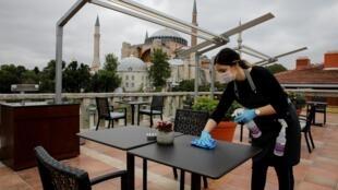 A l'hôtel Sultanahmet d'Istanbul, une employée désinfecte une table conformément aux dispositions sanitaires liées au coronavirus.