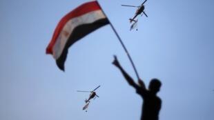 Des hélicoptères de l'armée égyptienne déploient le drapeau national, applaudis par une foule réunie place Tahrir, le 1er juillet au Caire.