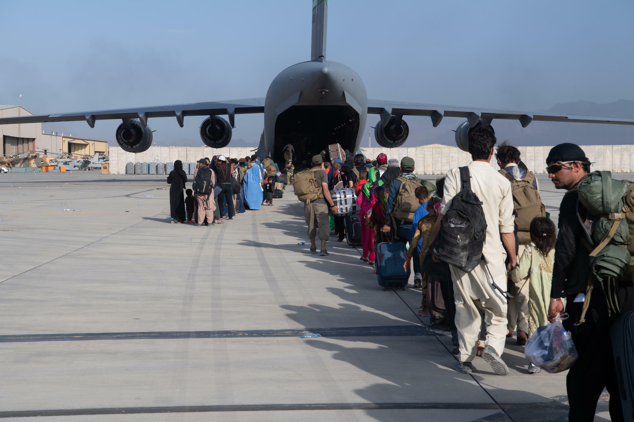 This handout photo courtesy ot the US Air Force shows passengers waiting to board a US air transport at Hamid Karzai International Airport (HKIA), Afghanistan, August 24, 2021