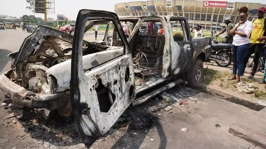 People inspect a burned police car after clashes outside Martyrs Stadium in Kinshasa on May 13, 2021