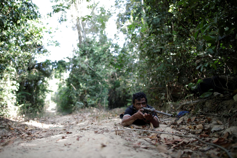 O líder indígena Paulo Paulino Guajajara segura uma arma durante a busca por madeireiros ilegais na terra indígena Arariboia, perto da cidade de Amarante, estado do Maranhão, Brasil, 11 de setembro de 2019.