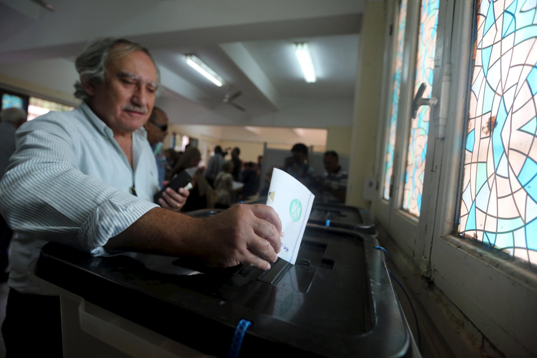 Eleitor deposita voto na urna em Giza, no interior do Egito, neste domingo (18).