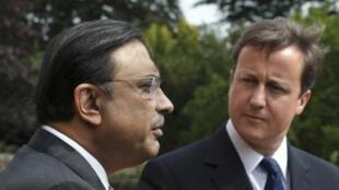 Britain's Prime Minister David Cameron watches Pakistan's President Asif Ali Zardari speak to media at Chequers
