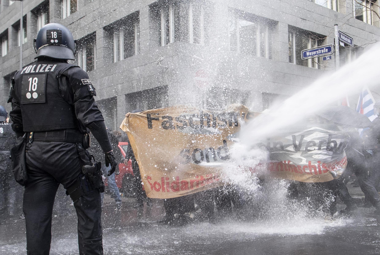 """Manifestção antimáscara na Alemanha, convocada pelo movimento """"Querdenker"""", que reuniu quase mil pessoas em Frankfurt em novembro de 2020, foi dispersada pela polícia com jatos de água.  En Allemagne, près d'un millier d'anti-masques avaient défilé samedi à Francfort à l'appel d'un collectif «Libre penseur». La police a utilisé des canons à eau pour disperser des contre manifestants."""