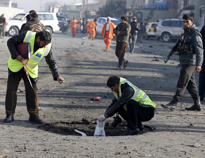 Сотрудники безопасности на месте взрыва в районе аэропорта Кабула, 28 декабря 2015 г.