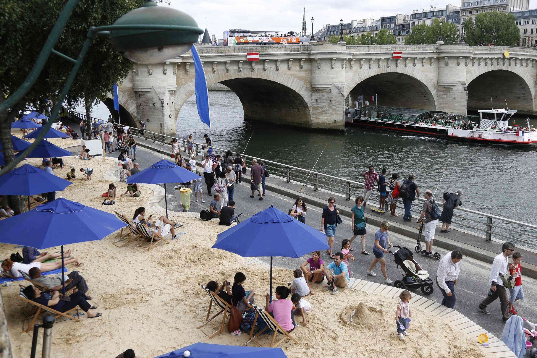 "People relax as ""Paris Plages"" (Paris Beach) opens along the banks of River Seine in Paris, France, July 20, 2015."